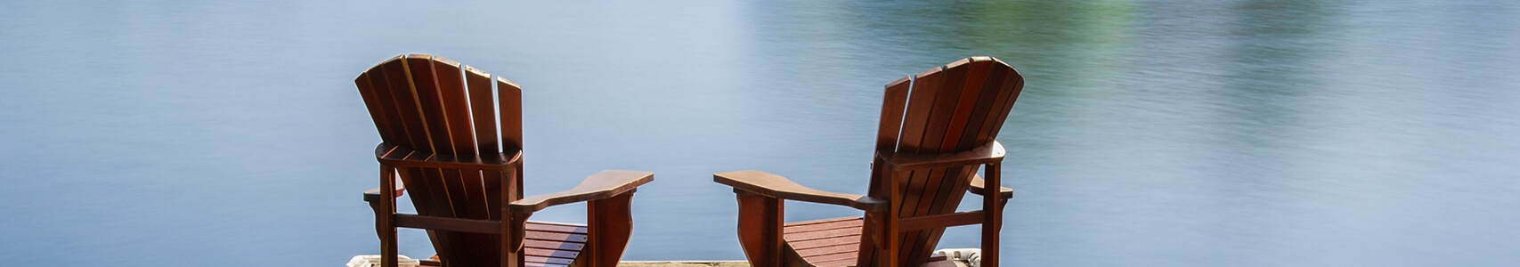 Two chairs sitting outside by a lake
