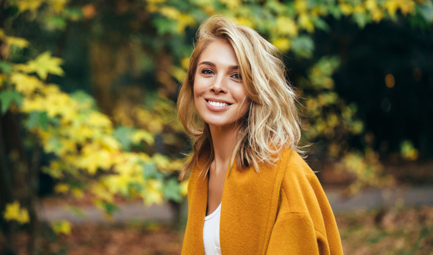 Blonde woman with dental implants smiles while wearing a golden pea coat outside by the fall leaves