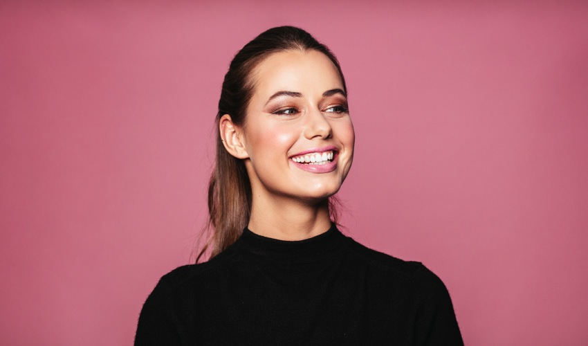 Brunette woman in a black shirt smiles against a pink background after overcoming her dental anxiety