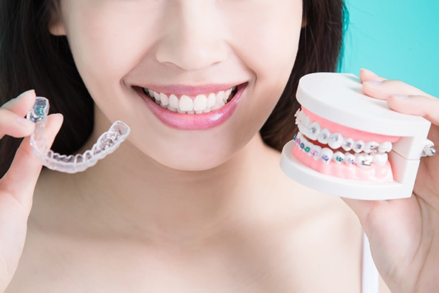 woman holding clear aligners and traditional braces