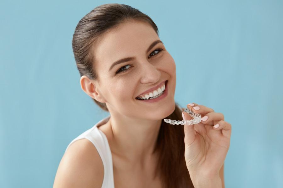 Smiling brunette girl holding a clear aligner like Invisalign