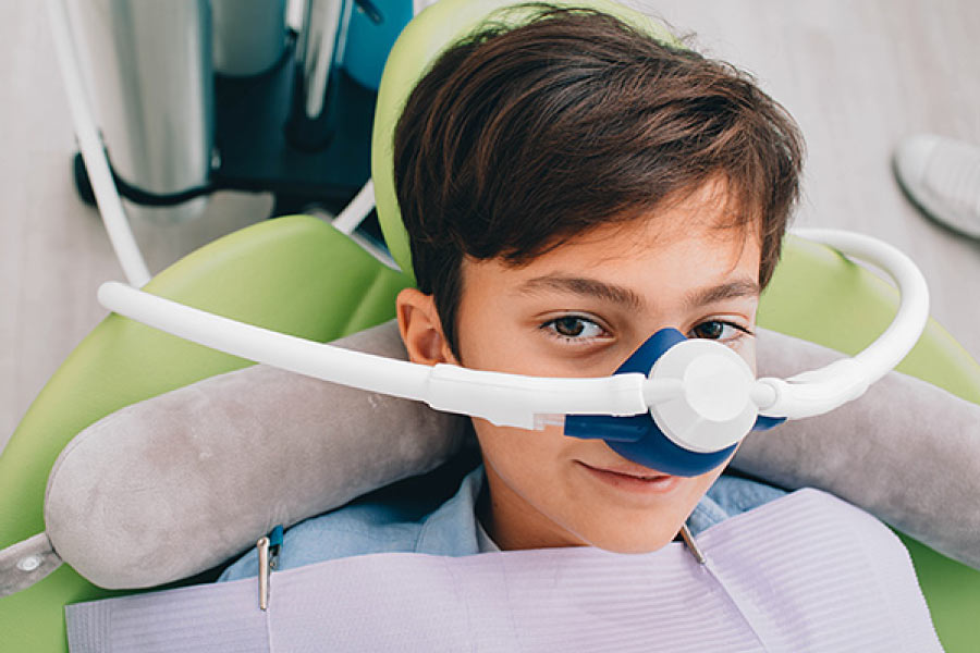Photo of a boy in the dental chair receiving nitrous oxide sedation through a nose piece.
